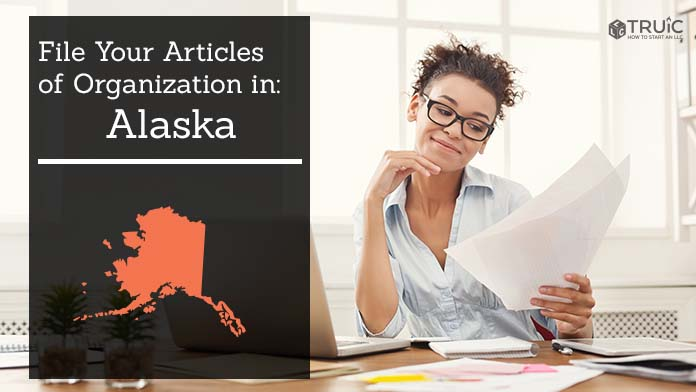 Woman smiling while looking at her articles of organization for Alaska.