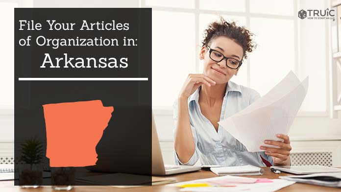 Woman smiling while looking at her articles of organization for Arkansas.