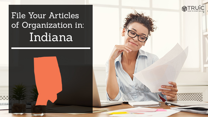 Woman smiling while looking at her articles of organization for Indiana.