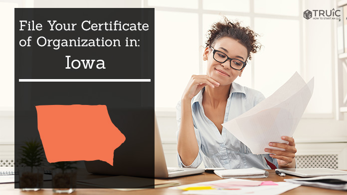 Woman smiling while looking at her certificate of organization for Iowa.