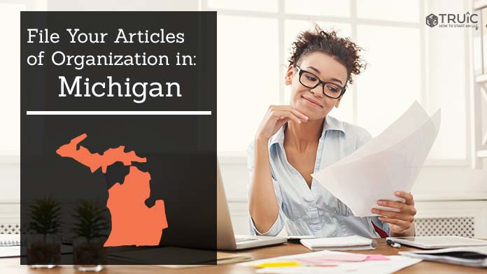 Woman smiling while looking at her articles of organization for Michigan.