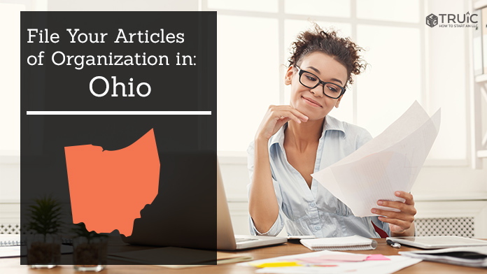 Woman smiling while looking at her articles of organization for Ohio.