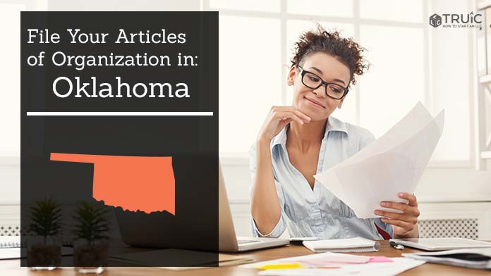 Woman smiling while looking at her articles of organization for Oklahoma.