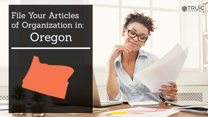Woman smiling while looking at her articles of organization for Oregon.
