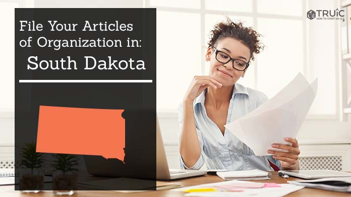 Woman smiling while looking at her articles of organization for South Dakota.