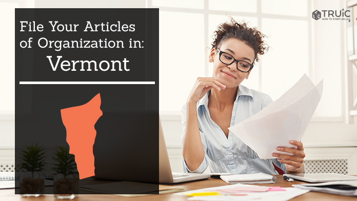 Woman smiling while looking at her articles of organization for Vermont.