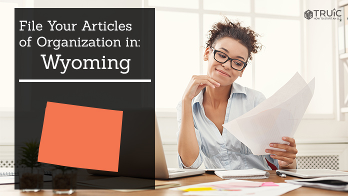 Woman smiling while looking at her articles of organization for Wyoming.