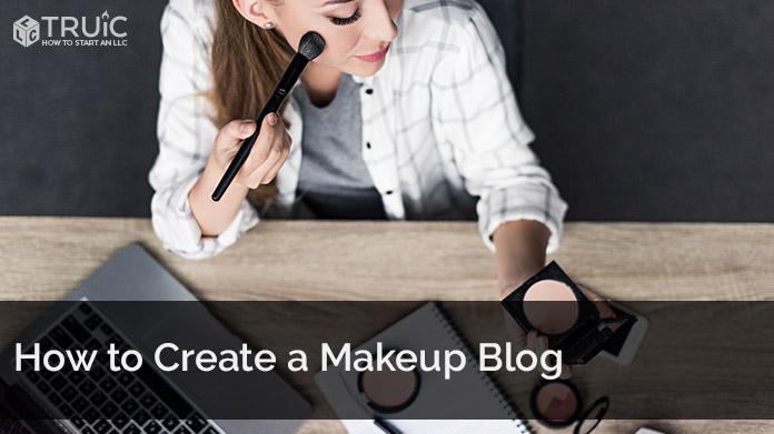 A woman applying makeup at her laptop