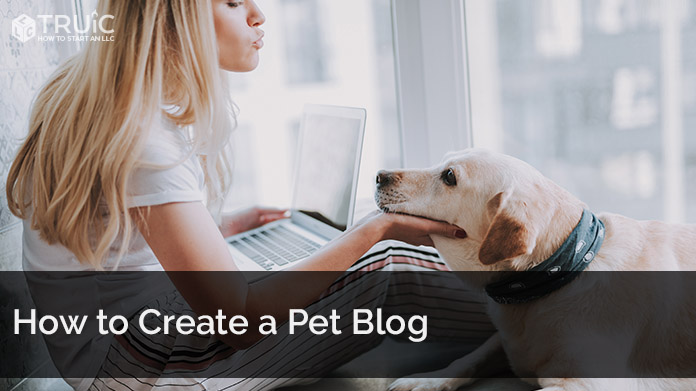 A woman on her laptop making faces at her dog