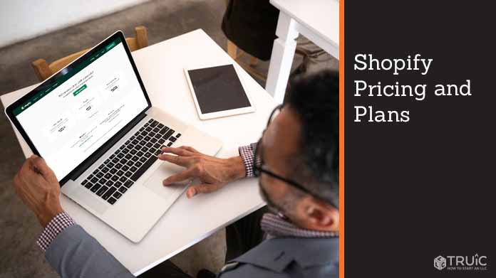 Person on laptop looking at Shopify's pricing and plans.