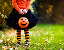 A child stands wearing a Halloween costume while clutching a pumpkin bucket