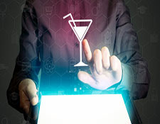 A man manipulates a digital projection of a martini glass coming from a tablet