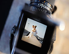 A camera's viewfinder shows a bride and groom