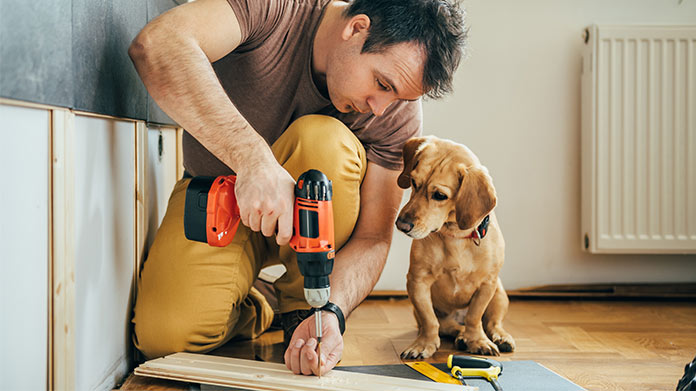 A man drilling into a wood plank while sitting next to a dog.