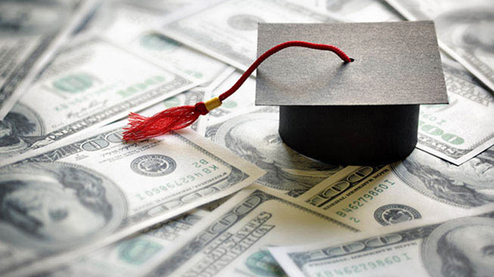 A paper graduation cap sitting on top of many one hundred dollar bills