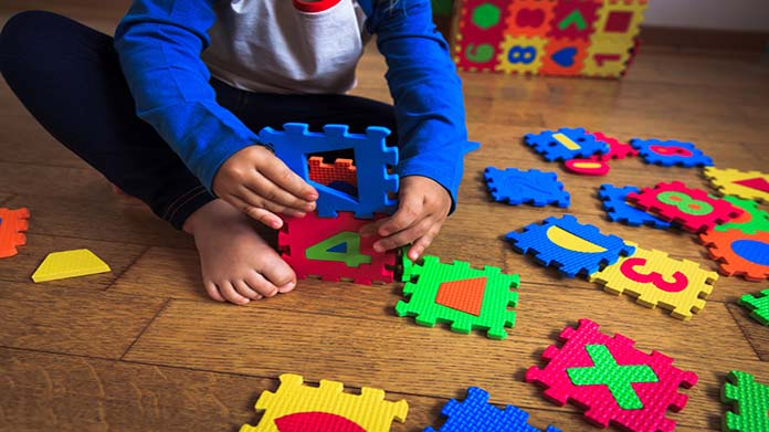 Image of child playing with colorful puzzle blocks