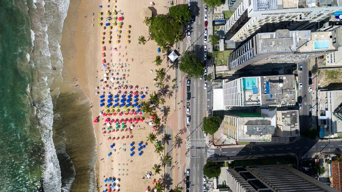 An aerial shot of buildings and people on a beach