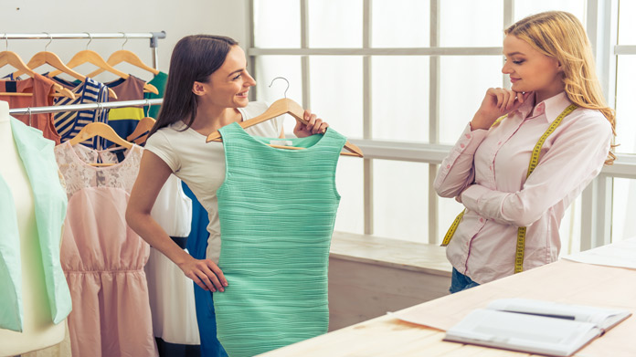 A woman showing another woman a green dress from a rack