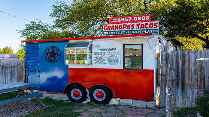 "Image of food truck with a sign that reads ""Grandpa's Tacos"""
