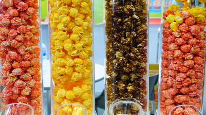 Four different flavors of gourmet popcorn in plastic tube containers