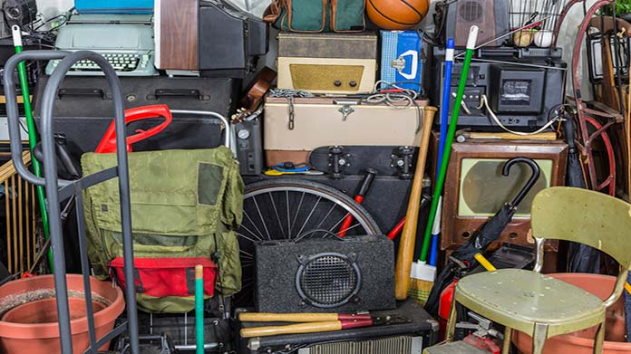 Many cluttered items including a speaker, a backpack, a baseball bat and a typewriter