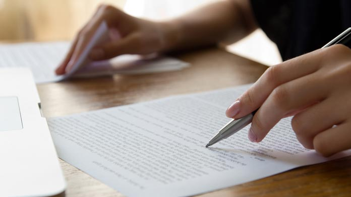 A person marking up papers on a desk