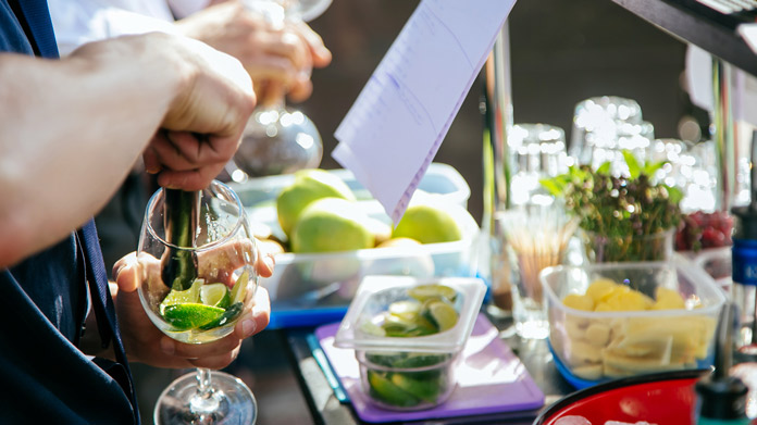 Close-up of bartender muddling a lime
