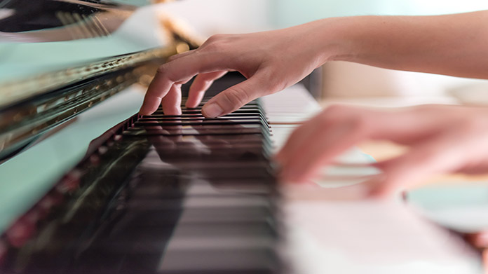 Music Lessons Business Idea: A closeup of a person playing piano