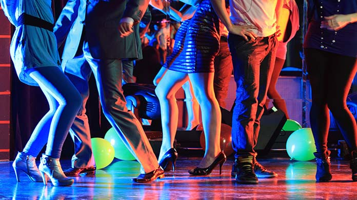 Image of several people's legs on dance floor