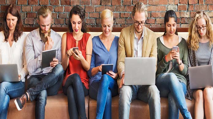 Group of seven people sitting on couch, each holding a tablet, smartphone or laptop.