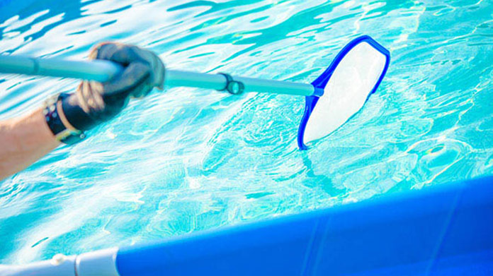 Pictured of someone cleaning a pool with a water skimmer