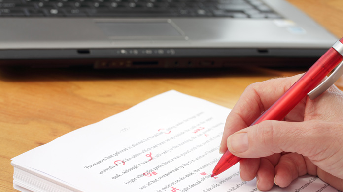 Hand holding a red pen making corrections on a printed document