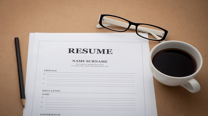 Image of resume template sitting on desk next to a cup of coffee and pair of reading glasses.