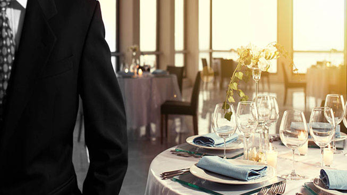 Man with suit standing inside restaurant in early day