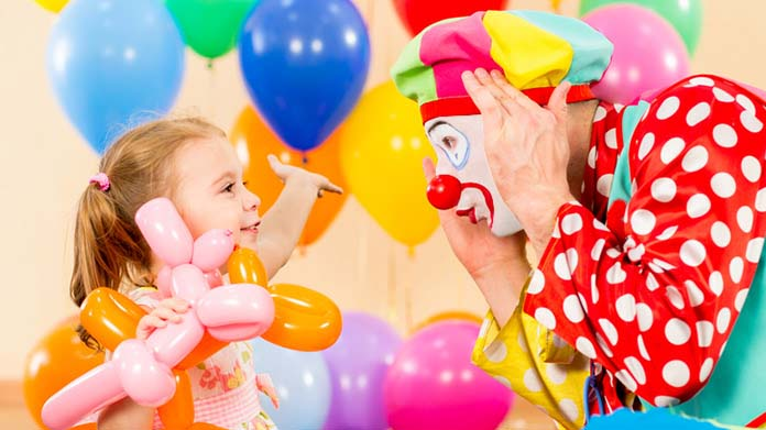 A child plays peek-a-boo with a clown, surrounded by balloons