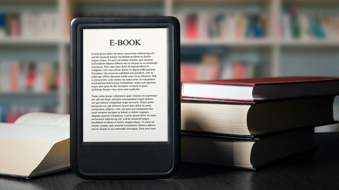 "Tablet that reads ""EBOOK"" on the screen, propped up against a pile of books."