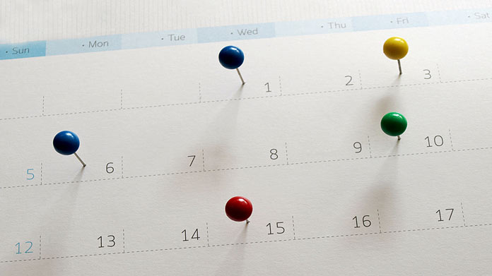 Image of calendar with colorful pins in it