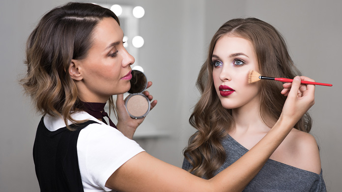 Makeup artist applying makeup to a model with a brush