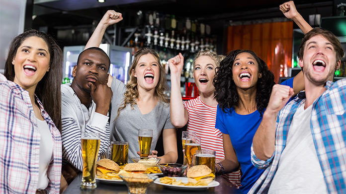 Several people cheering wile eating food and drinking beer in a sports bar