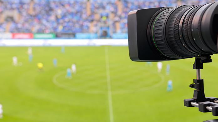 Camera sitting on a tripod above a sporting event