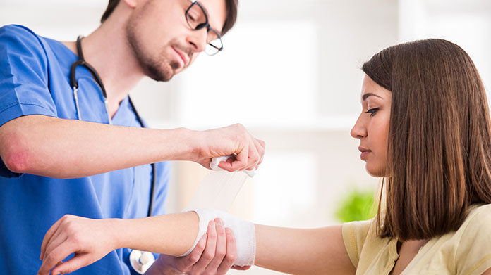 nurse wrapping a patients arm in gauze
