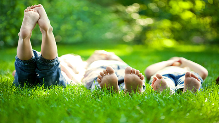 Three children lying in the grass on a sunny day with one raising his legs in the air