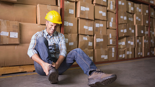 A man in a hard hat sits near a wall of boxes clutching his ankle in pain