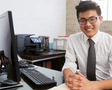 A smiling man sits at a computer and learns about corporate veils