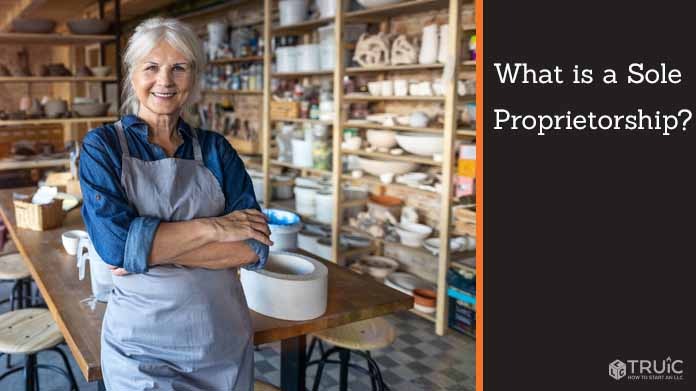 A confident sole proprietor stands in the forefront of her art studio.