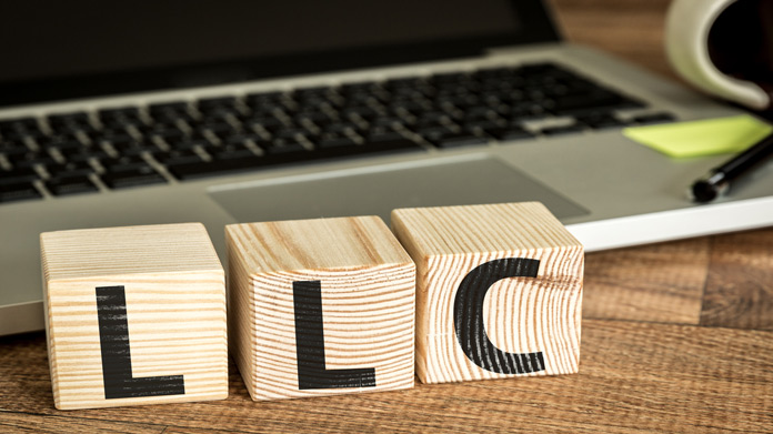 "Three wooden blocks painted with ""LLC"" in front of a laptop"