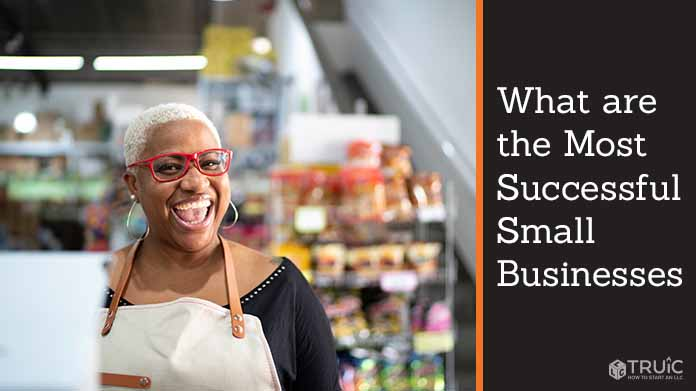 Female small business owner with a large smile and red glasses.