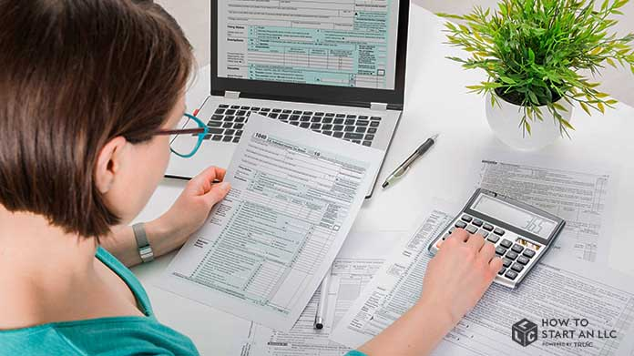 A woman is bookkeeping while using a calculator and a laptop