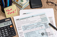 "LLC Taxes: A cluttered desk with tax forms, a calculator, and more with a sticky note saying ""TAX TIME!"""