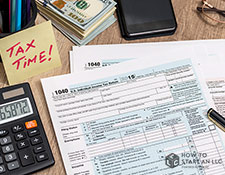 "A desk with tax forms, a calculator, and more with a sticky note saying ""TAX TIME!"""